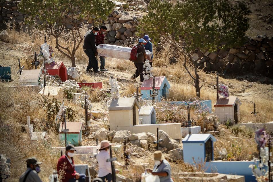 Menschen mit Mundschutzmasken tragen einen Sarg bei einre Beerdigung auf dem Friedhof El Cebollar inmitten der Corona-Pandemie.