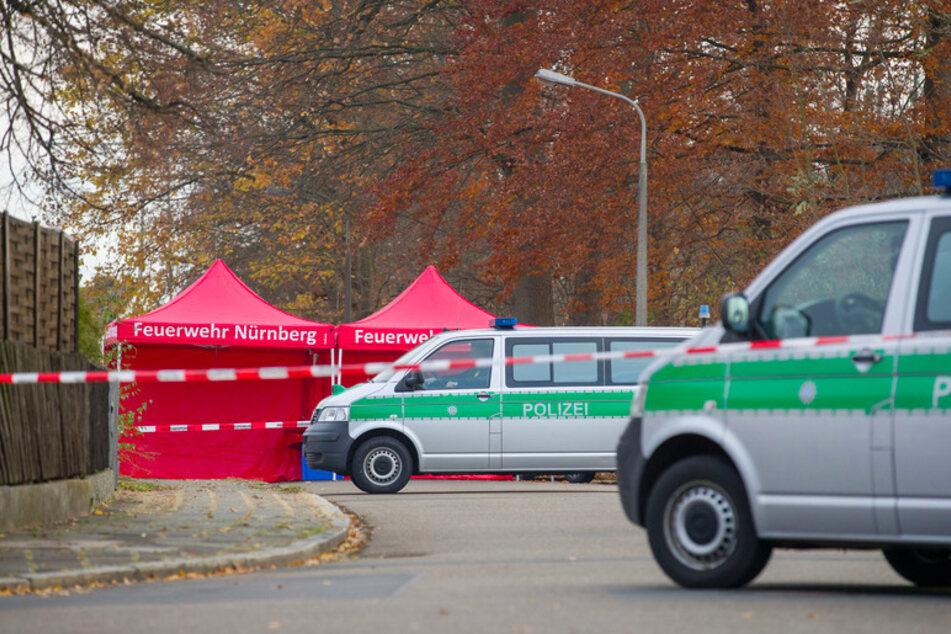 Polizisten bewachen die Zufahrt einer Straße, in der zuvor zwei Menschen erschossen wurden.