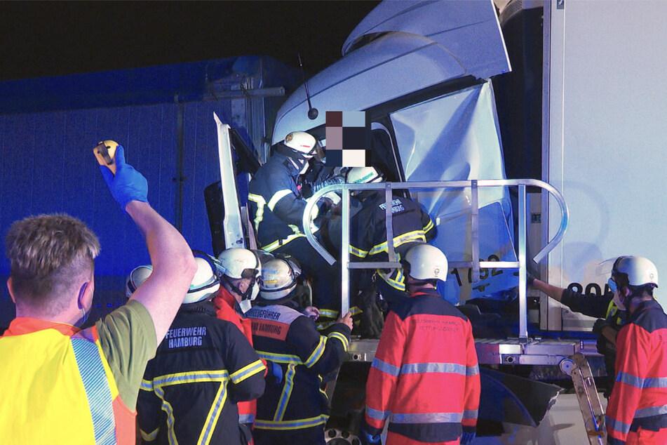 Der verletzte Fahrer wird aus dem Fahrerhäuschen befreit.
