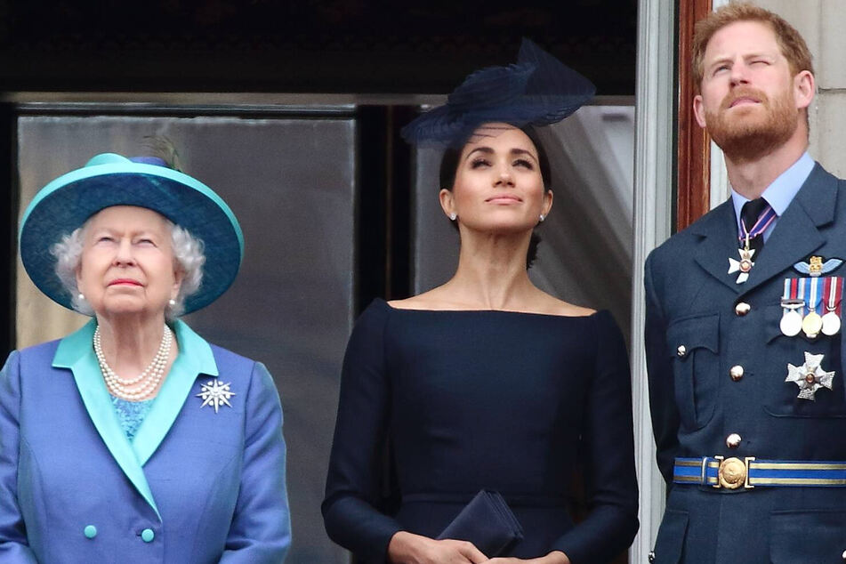 Those were the days: Queen Elizabeth II; her grandson, Prince Harry; and his wife, Duchess Meghan, stand on a balcony as Royal Air Force planes fly over Buckingham Palace in July 2018.