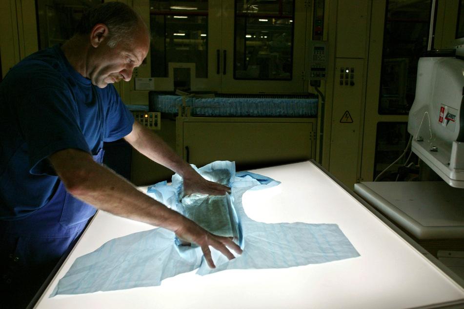 Im Werk Herbrechtingen (Landkreis Heidenheim) der Paul Hartmann AG prüft ein Mitarbeiter die Qualität einer Inkontinenz-Windel auf einer Leuchtplatte. (Archiv)
