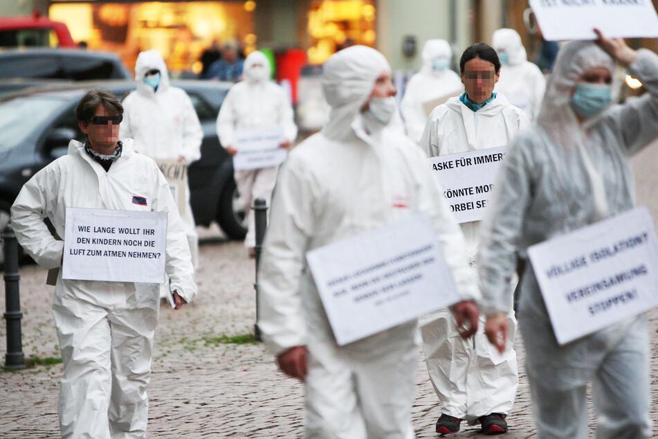 Vor den Spaziergängen waren etwa 15 Personen mit weißen Schutzanzügen und Transparenten in Pirna unterwegs.