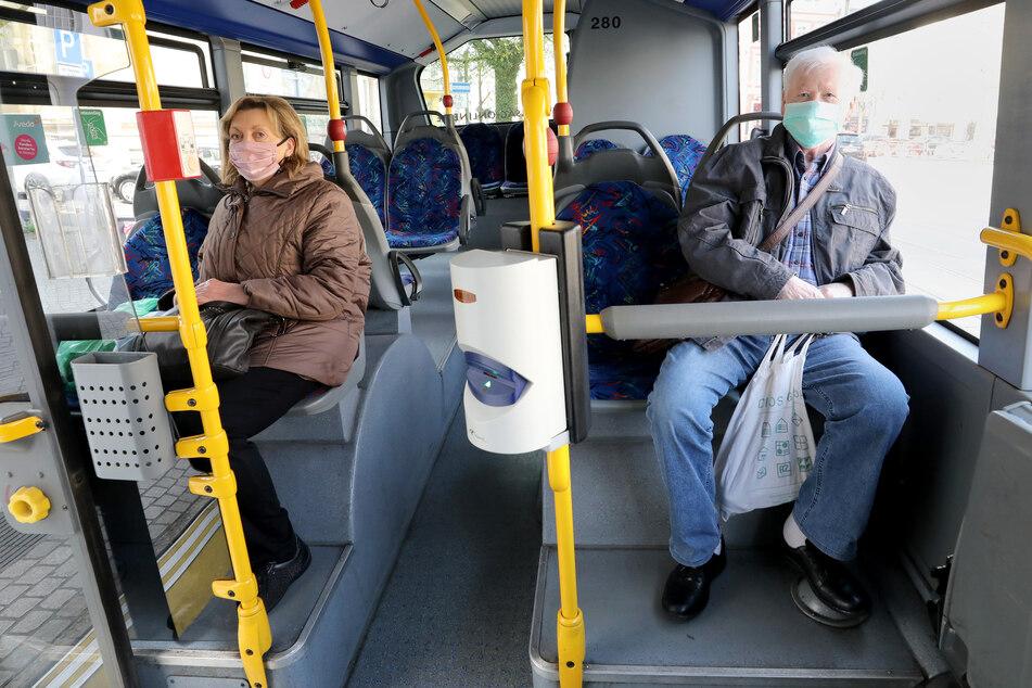 Fahrgäste sitzen mit Mund-Nasenbedeckung in einem Bus.