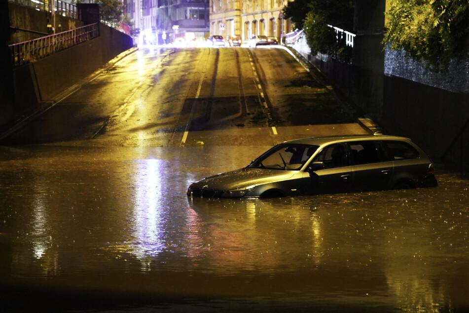 Ein abgesoffenes Auto steht in der überfluteten Autounterführung am Österreichischen Platz in Stuttgart. Ein starkes Unwetter ist über weite Teile Baden-Württembergs hinweggezogen und hat dabei große Schäden angerichtet.