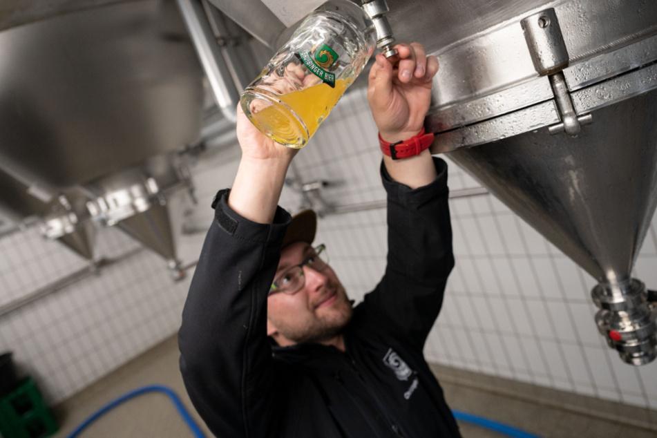 Christoph Hilsenbeck, Braumeister der Lammbrauerei Hilsenbeck GmbH & Co KG, entnimmt zum Verzehr gedachtes Bier aus einem Tank.