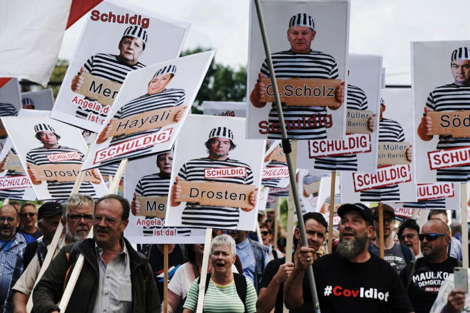 """Teilnehmer einer Demonstration gegen die Corona-Maßnahmen halten Schilder mit Fotos von Politikern, Journalisten und Wissenschaftlern jeweils mit Namen und """"Schuldig""""."""