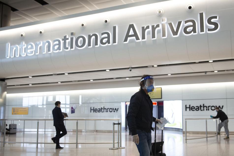 London: Ein Fluggast mit einem Mundschutz und einem Visier geht durch den Flughafen Heathrow.