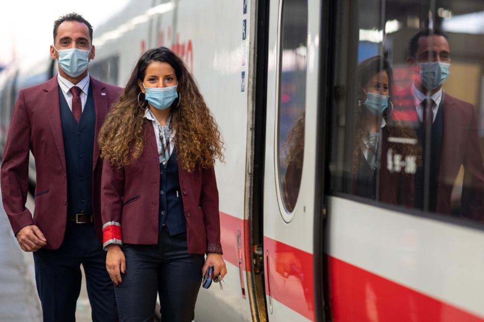 Zwei Zugbegleiter stehen in der neuen Bekleidung der Deutschen Bahn neben einem ICE, der von Stuttgart in das Ostseebad Binz fährt. Kreiert wurde die Bekleidung vom Designer Guido Maria Kretschmer.