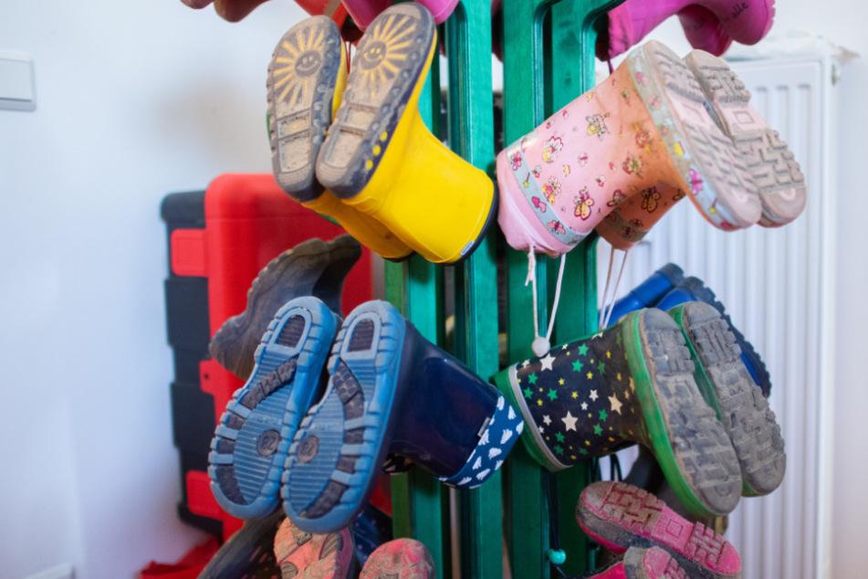 Gummistiefel von Kindern hängen in einem Kindergarten.