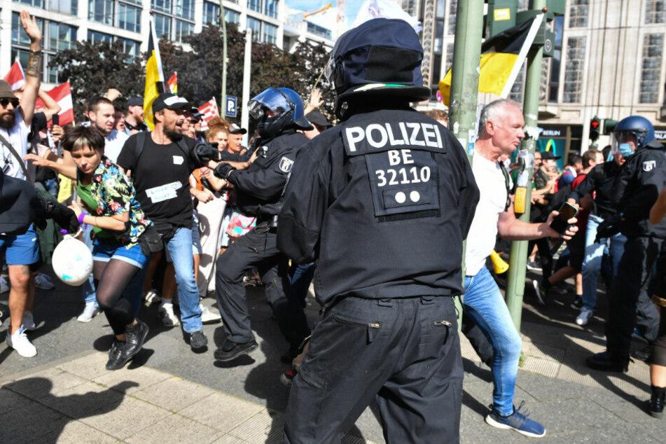 Teilnehmer einer Demonstration gegen die Corona-Maßnahmen durchbrechen eine Polizeikette an der Ecke Friedrichstraße/Reinhardtstraße