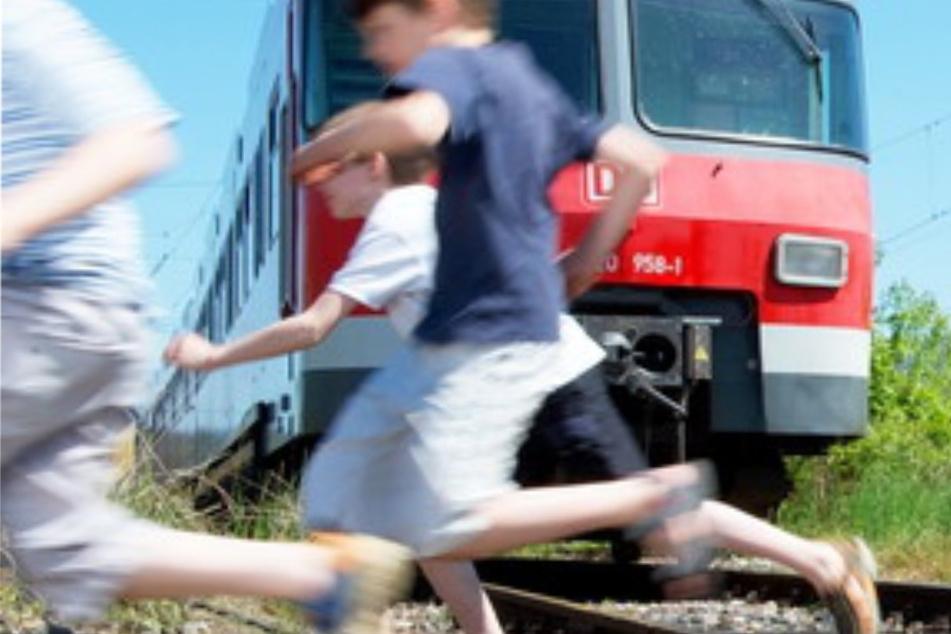Kinder spielen auf Bahngleis, dann rast ein Zug heran