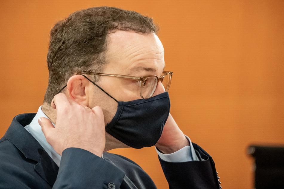 Jens Spahn (CDU), der Bundesminister für Gesundheit, nimmt vor Beginn der Sitzung des Bundeskabinetts im Kanzleramt seine Maske ab.