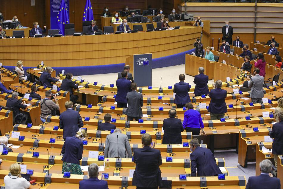 Abgeordnete des Europäischen Parlaments stehen im Parlamentssaal.