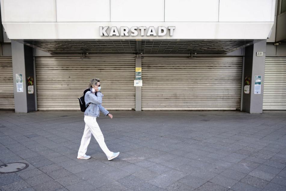 Eine Passantin mit Mund-Nasenschutz geht am Mittag am Kurfürstendamm an einer geschlossenen Karstadt-Filiale vorbei.