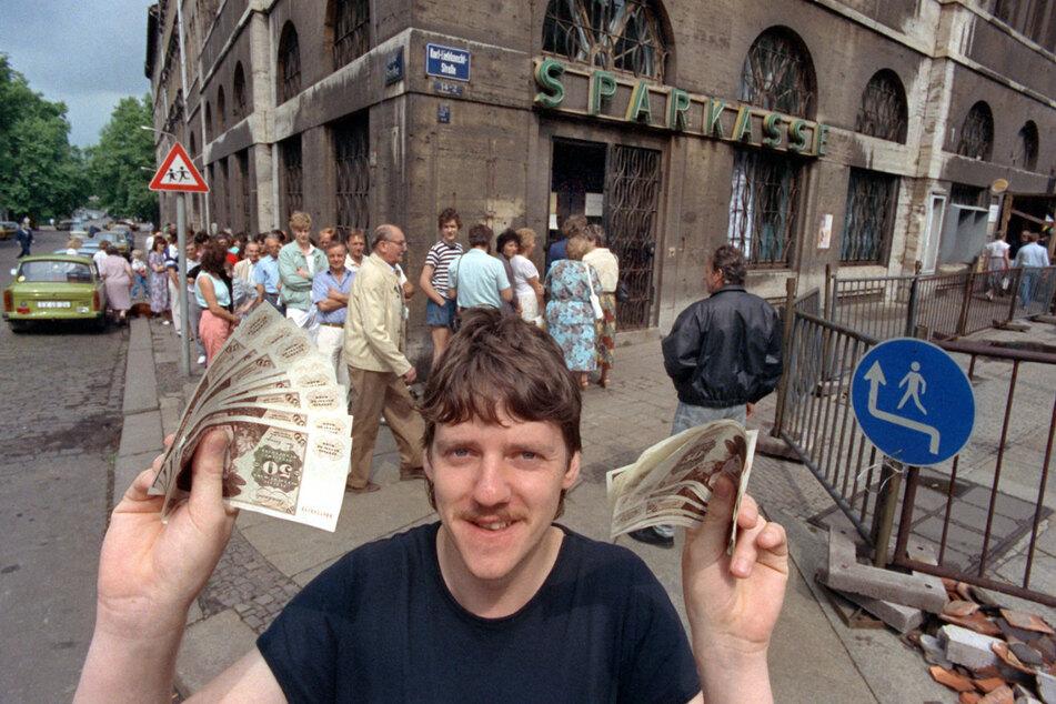Nach langem Schlangestehen vor einer Leipziger Bank freut sich dieser junge Mann über seine D-Mark-Banknoten, aufgenommen am 1. Juli 1990, der Tag der deutsch-deutschen Währungsunion.