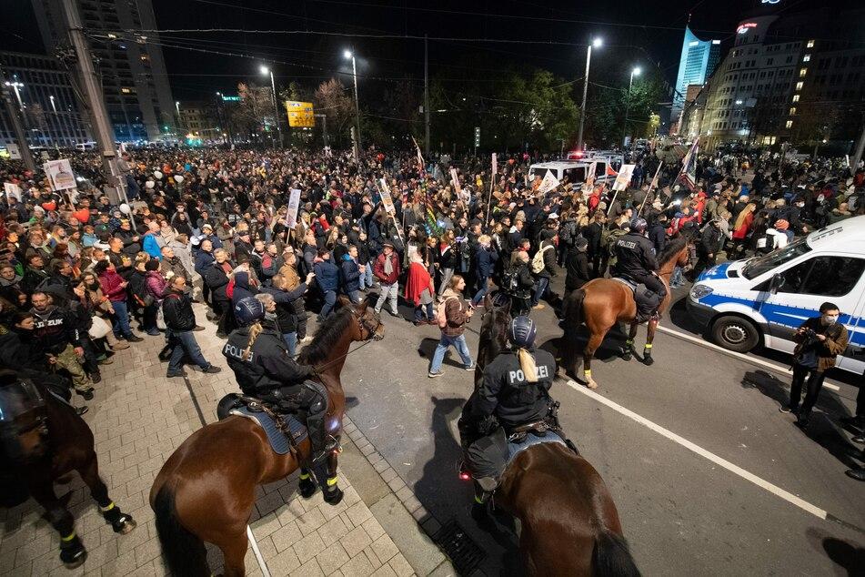"""07.11.2020, Sachsen, Leipzig: Teilnehmer stehen nach dem Ende einer Demonstration der Stuttgarter Initiative """"Querdenken"""" am Hauptbahnhof hinter der Reiterstaffel der Polizei."""