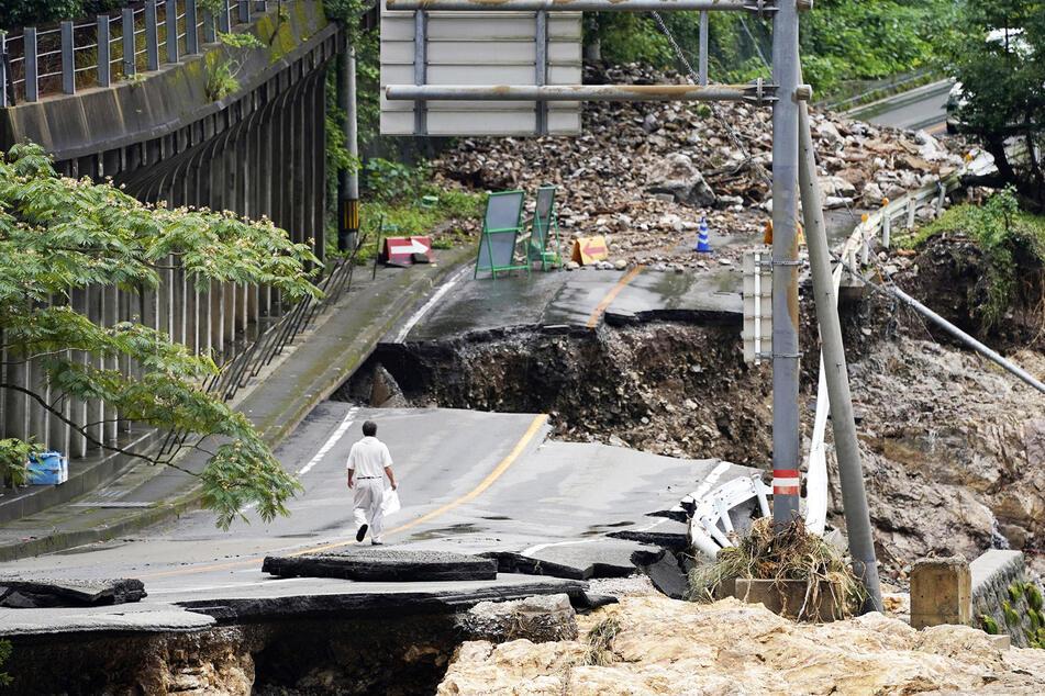 Ein Mann geht auf einer stark beschädigten Straße in Kumamura.