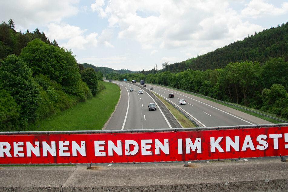 """Ein Banner mit der Aufschrift """"Rennen enden im Knast!"""" hängt an der A8."""