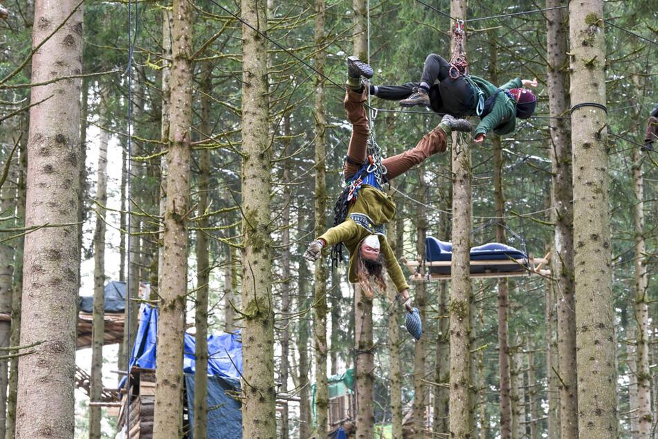 Die Klimaschützer hängen im Camp der Klimaschützer an einem Seil, das zwischen Bäumen gespannt ist.