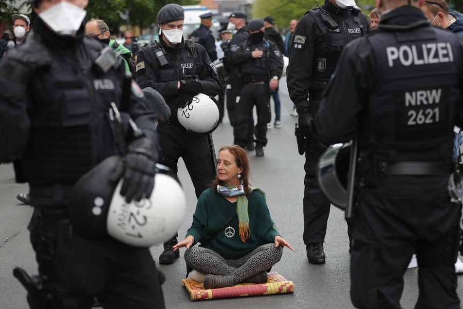 Eine Yoga-Treibende ist von Polizisten umzingelt.