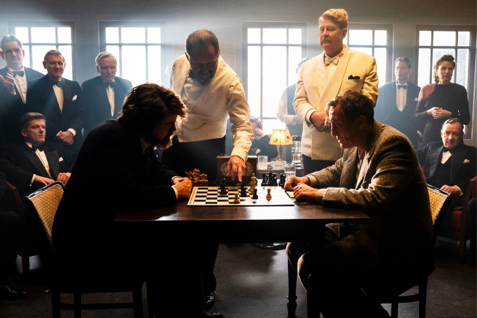 Alfred Koller (Samuel Finzi, 55, v., 2.v.l.) und Owen McConnor (Rolf Lassgard, 66, v., 2.v.r.) schauen Mirko Czentovic (Albrecht Schuch, 36, v.-l.) und Dr. Josef Bartok (Oliver Masucci, 52) bei einer Schachpartie auf hohem Niveau zu.