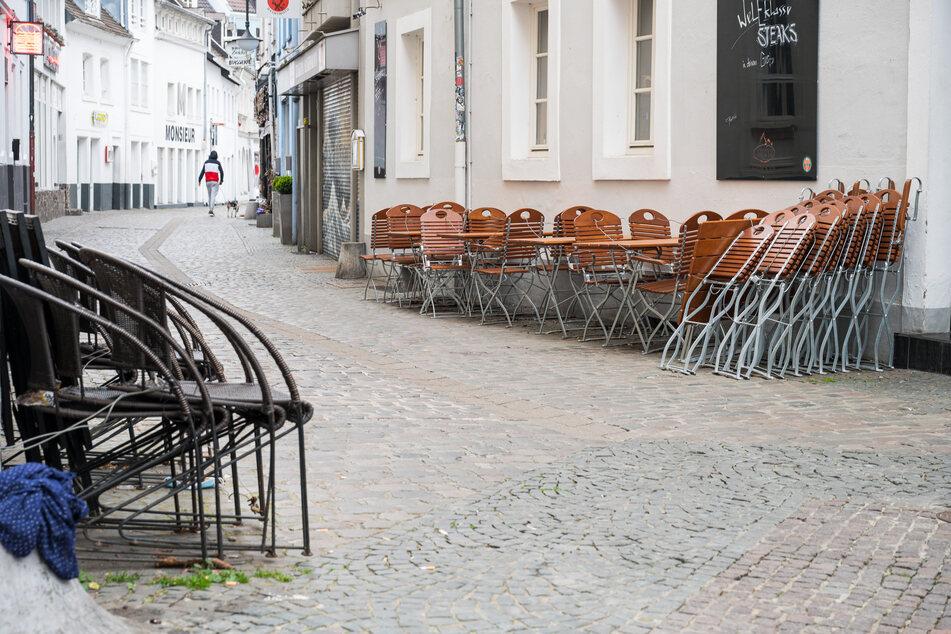 In der Innenstadt von Saarbrücken stehen im Außenbereich einer Gastronomie Stühle. Am heutigen Dienstag darf die Außengastronomie unter Auflagen wieder öffnen.