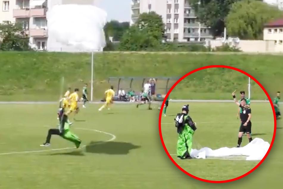 Fallschirm-Springer landet auf Fußballfeld, Schiedsrichter zeigt ihm die Gelbe Karte