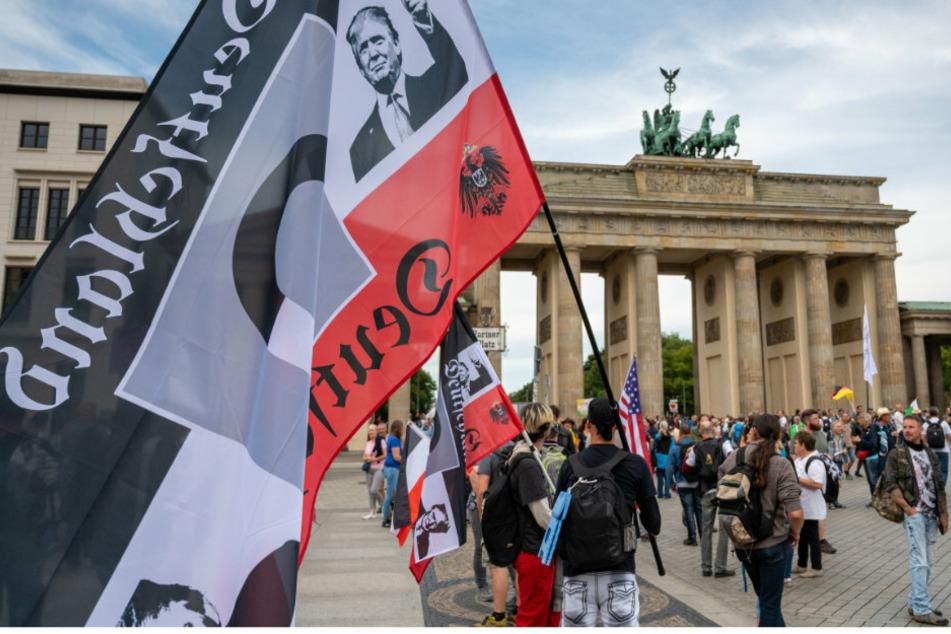 Ein Demonstrant hält vor einer Demonstration gegen die Corona-Maßnahmen eine große Reichsflagge vor dem Brandenburger Tor.