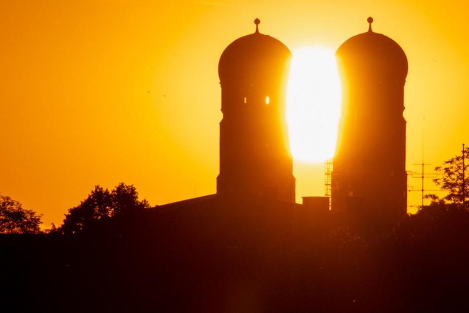 Die Sonne geht zwischen den Türmen des Münchner Liebfrauendoms auf.
