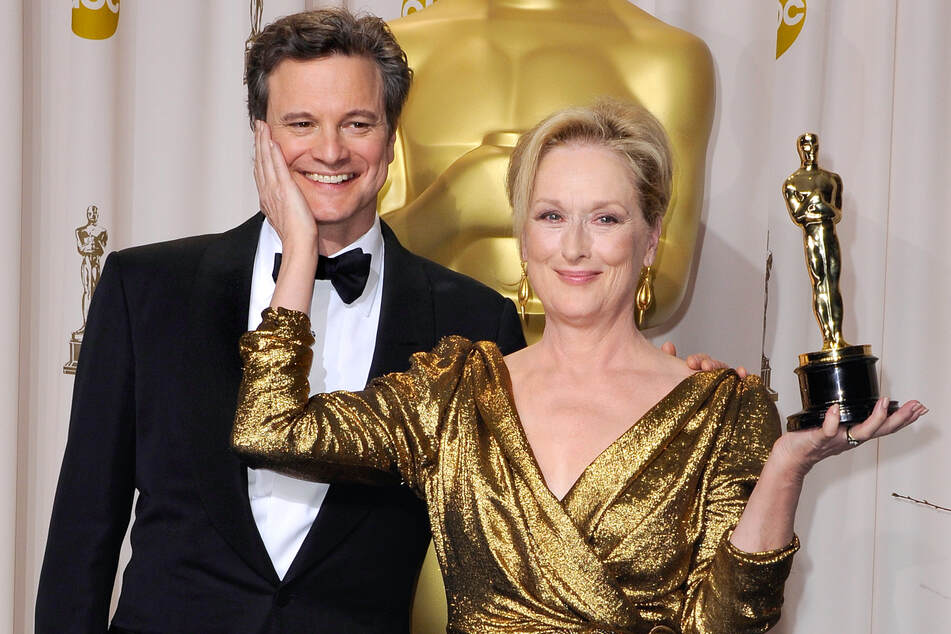 Meryl Streep holding the Oscar for her role in The Iron Lady, alongside Colin Firth during the 84th Academy Awards ceremony.