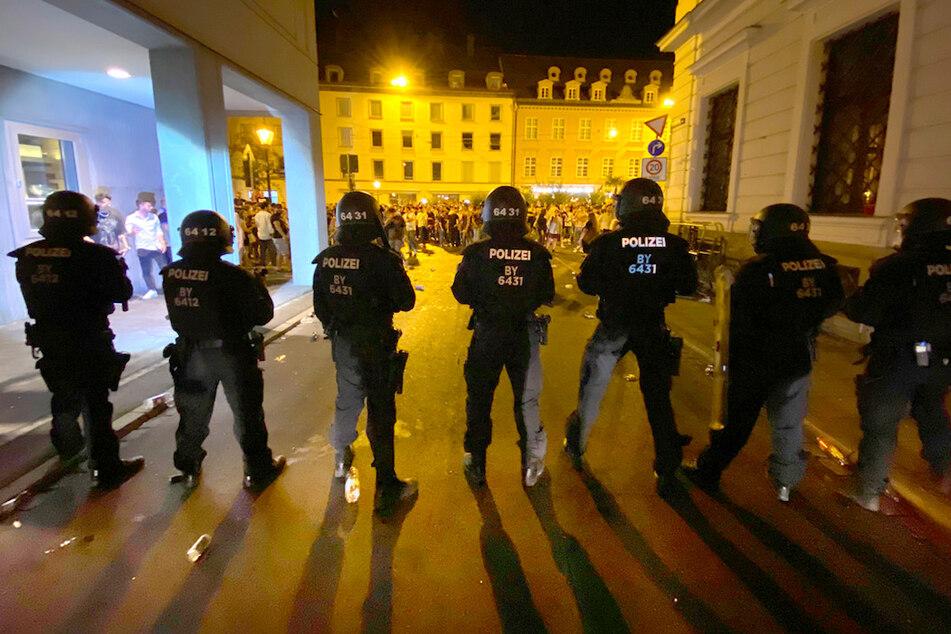 Polizisten stehen in der Augsburger Innenstadt, wo sich Menschen zum Feiern versammelt haben. Bei Räumungen eskalierte die Lage.