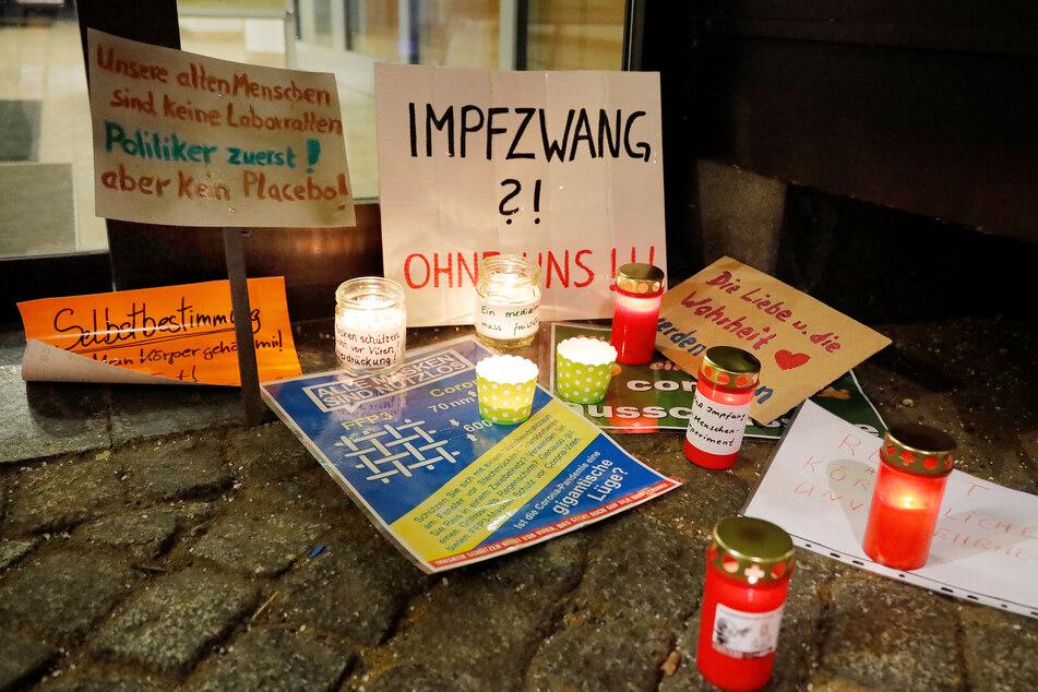 Impfgegner und Corona-Leugner stellten Kerzen und Plakate auf.