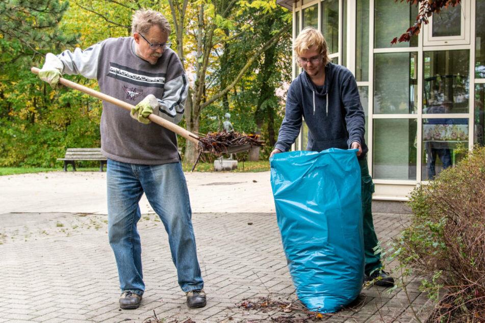 Räumen das nasse Laub am Bürgertreff weg: Wolfram Uhlmann (66, l.) und Paul Wodrig (22) sind gerne freiwillige Helfer.