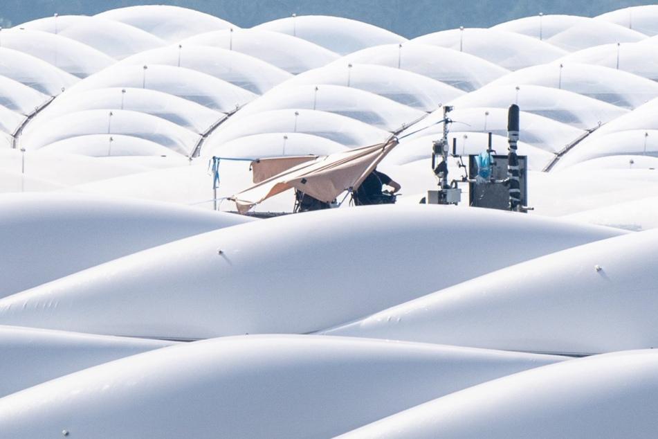 Polizisten sitzen unter einem Sonnenschutz auf dem Dach des Stadions in München.