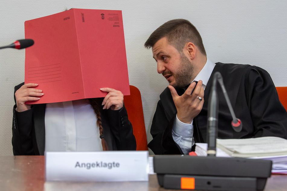 Die Angeklagte Jennifer W. hält auf ihrem Sitz im Gerichtssaals einen roten Aktendeckel vor ihr Gesicht. Neben ihr sitzt ihr Anwalt.