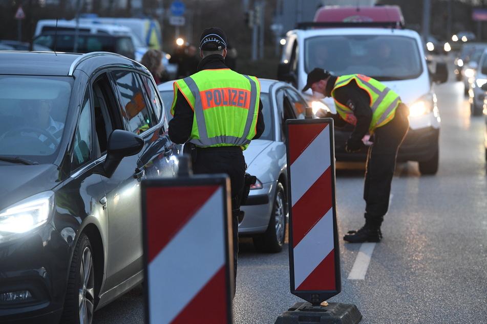 Polizeibeamte kontrollieren vor der Ziegelgrabenbrücke den Fahrzeugverkehr in Richtung der Insel Rügen.