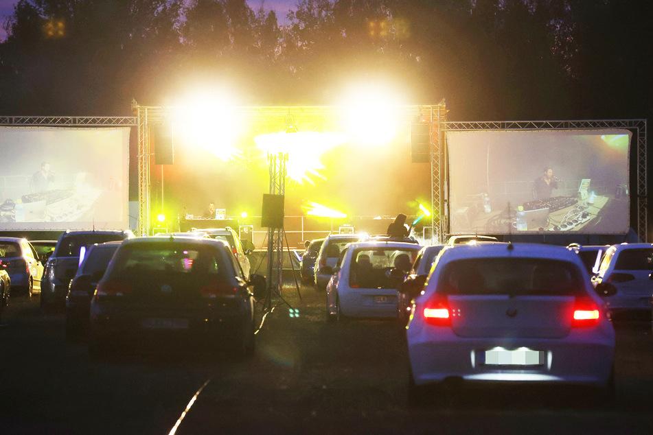 Besucher einer Autodisco im thüringischen Nobitz sitzen in ihren Fahrzeugen auf einer Wiese. (Symbolbild)