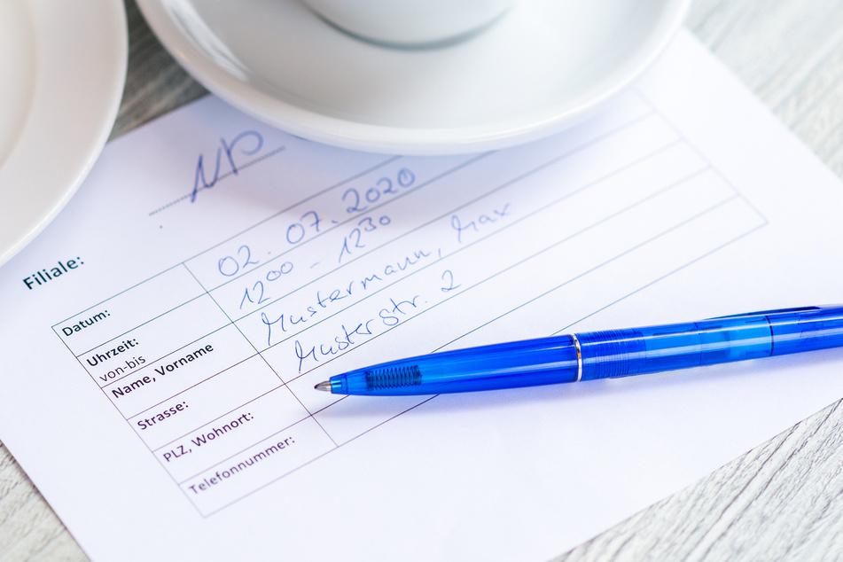 Ein Formular zur Erhebung der Kontaktdaten liegt in einem Café auf einem Tisch.