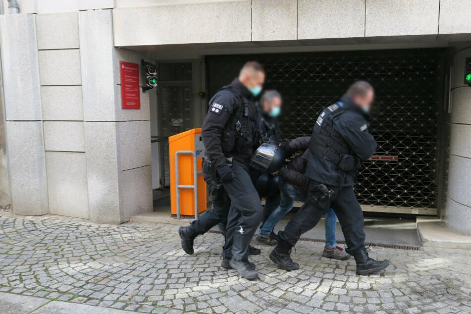 Die Polizei führt einen Mann ab.