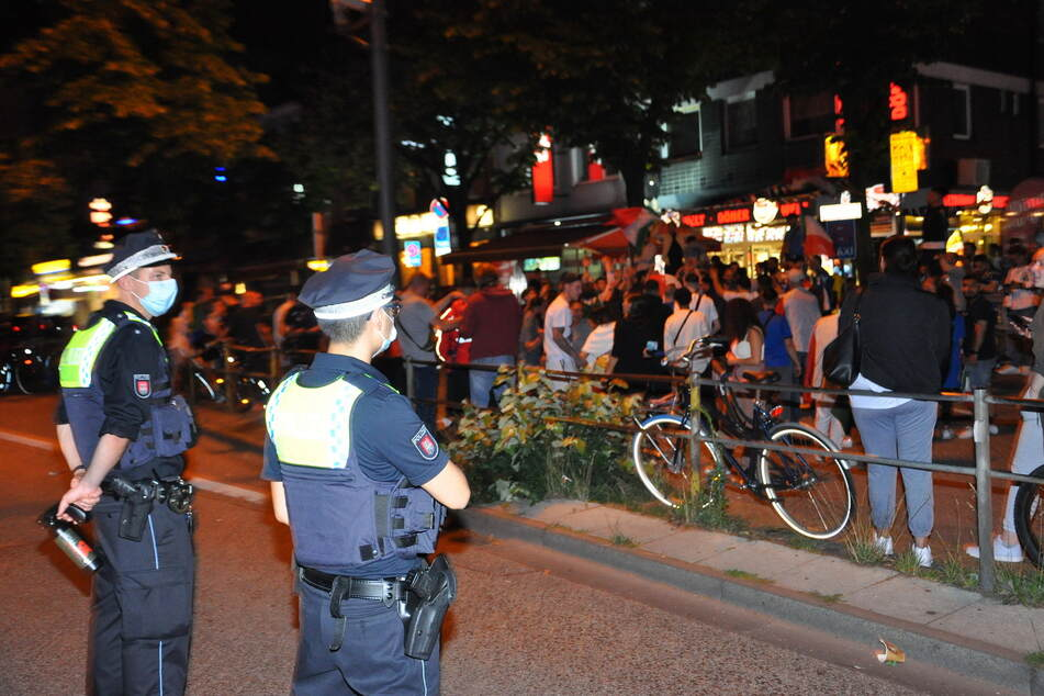 Zwei Beamte der Polizei beobachten das Geschehen auf der Hamburger Reeperbahn. Einige Hundert Menschen feierten dort den EM-Sieg der Italiener.