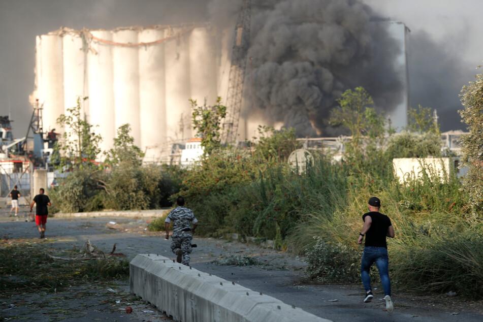 Sicherheitsbeamte laufen zum Ort der Explosion, während über dem Gebäude Rauch aufsteigt.