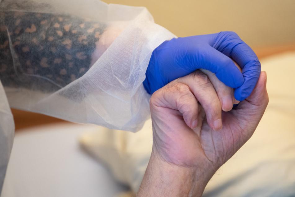 Eine Altenpflegerin in Schutzkleidung hält die Hand eines Bewohners.