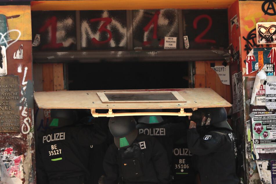 Mit schweren Geräten verschaffen sich die Polizisten gewaltsam Zutritt zu dem verbarrikadierten Haus.