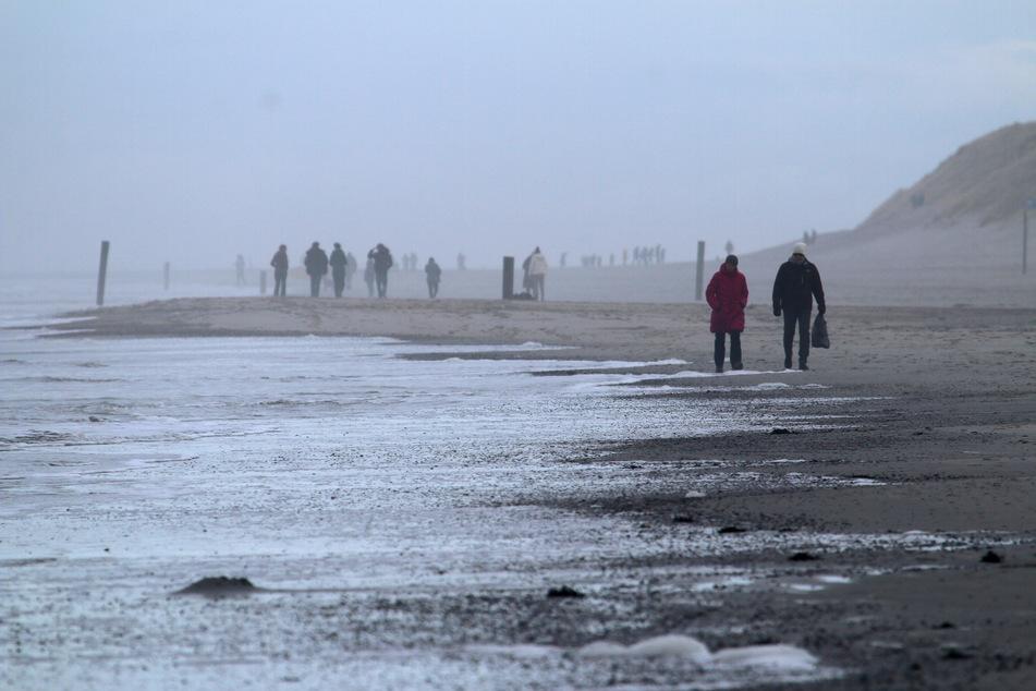 Spaziergänger sind am Weststrand der Nordsee-Insel unterwegs.
