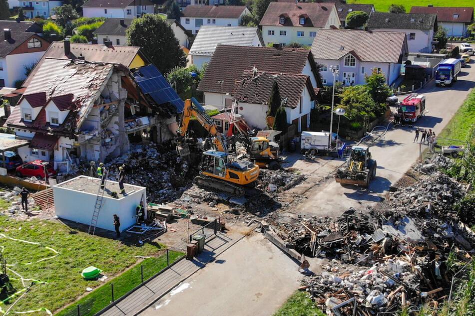 Zwei Bagger und ein Radlader sind bei Bergungsarbeiten an den Überresten eines Hauses im Einsatz, das am Donnerstag durch eine Explosion vollständig zerstört wurde.