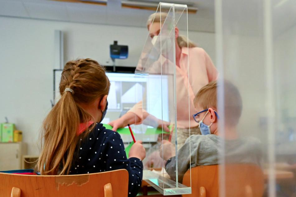 Kinder sitzen während des Unterrichts in einer Grundschulklasse mit Plexiglas-Trennscheiben zwischen den Plätzen an ihren Tischen.