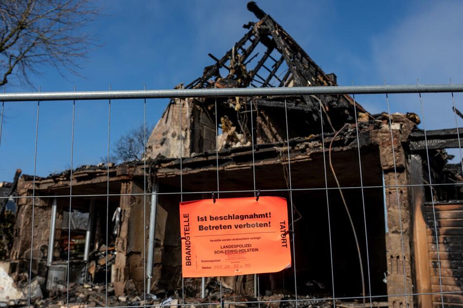 """Ein Hinweisschild mit der Aufschrift """"Ist beschlagnahmt. Betreten verboten"""" der Landespolizei hängt an einem Zaun vor den Überresten des bei der Explosion nahezu vollständig zerstörten Reihenendhauses."""