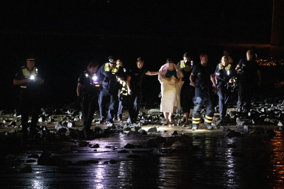 Polizisten begleiten die gerettete Schwangere sicher zur Straße.
