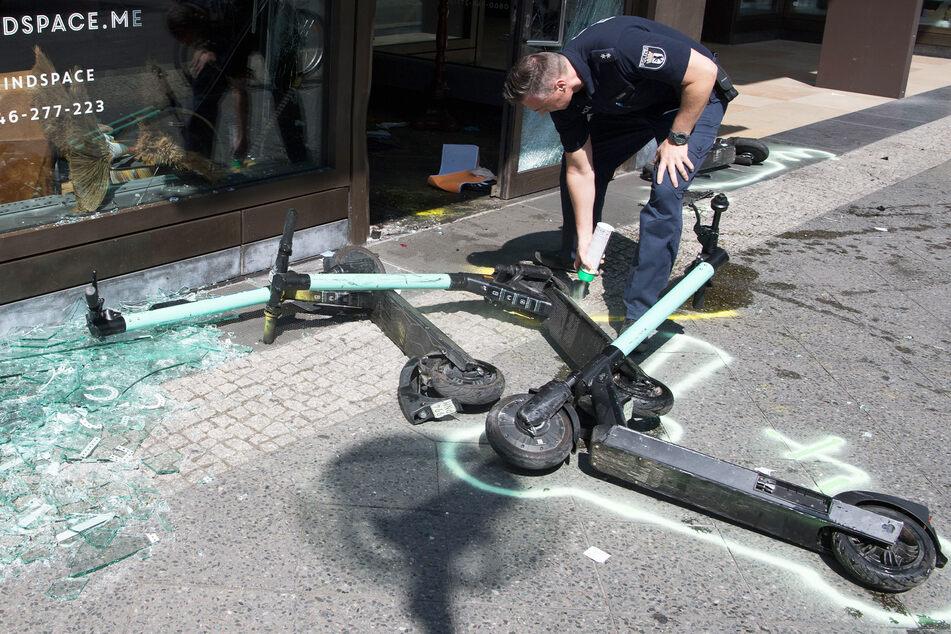 Ein Polizist markiert nach einem Verkehrsunfall E-Scooter.