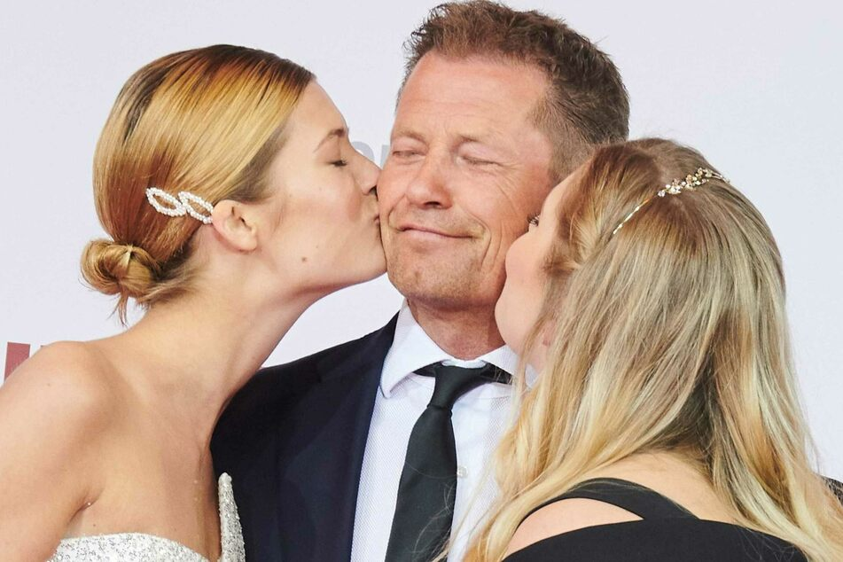 Der 57-Jährige genießt die Küsschen seiner Töchter Lilli (22, links) und Luna (24) auf einer Veranstaltung. (Archivbild)
